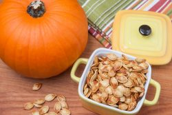 Toasted pumpkin seeds with a fresh pumpkin on a wooden cutting board
